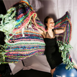 Woman holding a bright multicolored striped blanket, laughing