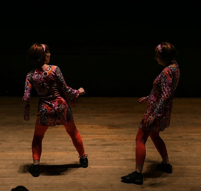 Two women in brightly colored dresses and wigs dancing