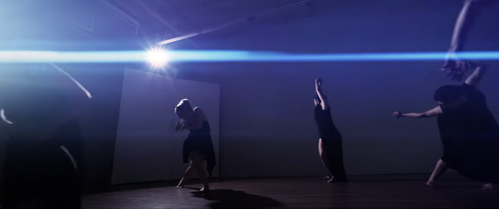 Four people dancing with a blue light sending streaks across the image