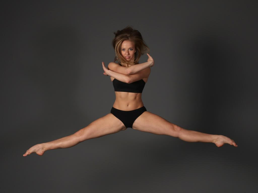 Woman jumping with her legs out to the side and her arms crossed in front of her