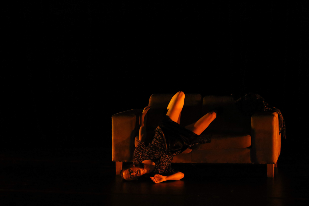 A woman sliding head first off a sofa bathed in red light