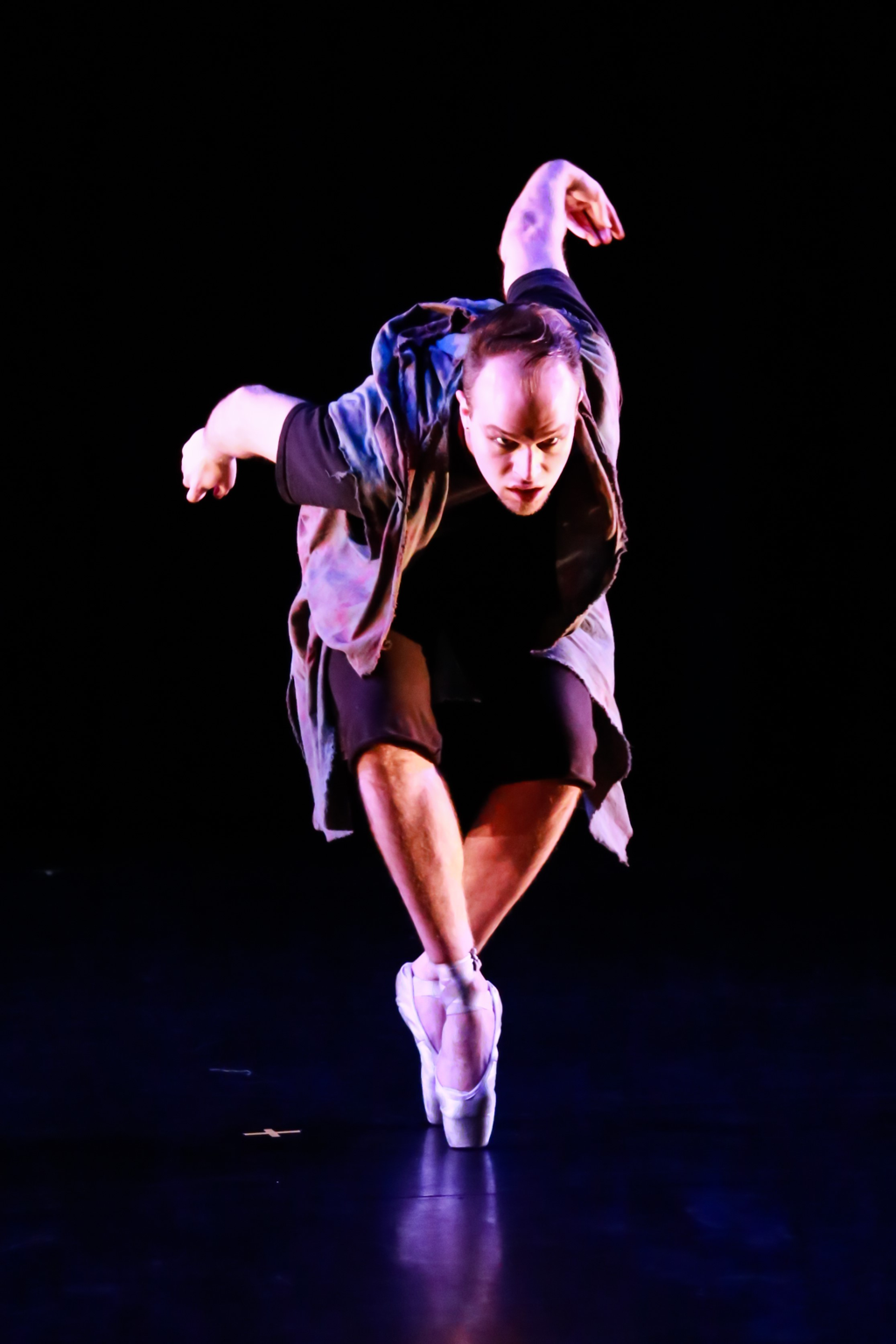 White man in pointe shoes Leaning forward in a crouch Arms extended back